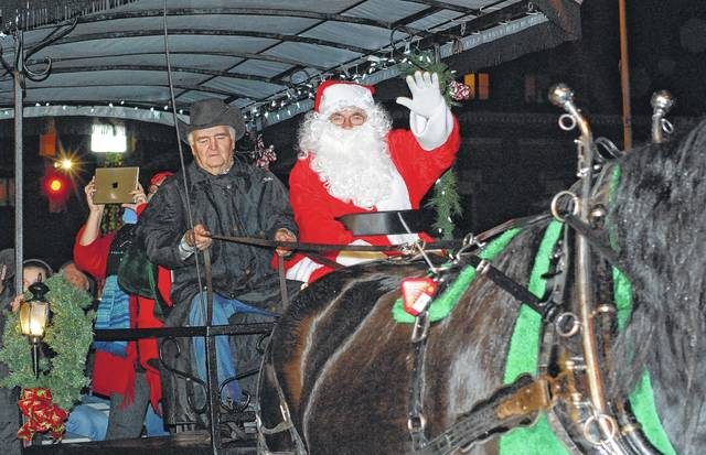 Santa arrives on a horse-drawn trolley in Urbana during the Holiday Horse Parade in 2015.