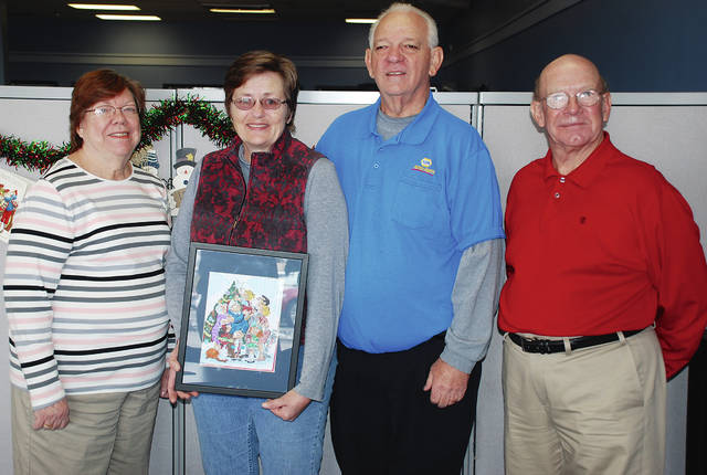 """Pictured from left are Eileen James, Joann Evans, Al Evans and Neil Evans. James and Neil Evans are volunteers with the Cancer Association of Champaign County (CACC). Joann and Al Evans are holding the custom-drawn 'Dennis the Menace"""" cartoon panel created by artist Ron Ferdinand especially for them after Al won a raffle benefitting the CACC."""