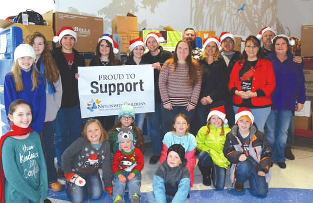 Tyler Slaven, at right of banner, holds a corner of the Nationwide Children's Hospital Banner. With him are family members and fellow volunteers who helped donate about 3,000 toys as part of his Christmas project.