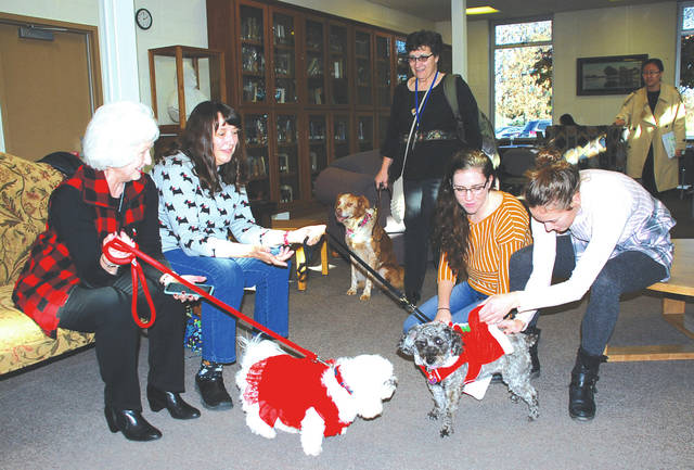 Sue Stephens, Nancy Sleeper and Terry Reeder, left to right, along with their therapy dogs visit the Urbana University library this week for the benefit of students stressed out by exams this week. Junior Madison Davis, kneeling, and sophomore Audrey Pumford are shown petting the pooches, who are registered with Alliance of Therapy Dogs.