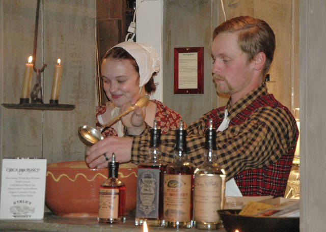 Cody Willoughby | Troy Daily News Samantha and Alek Martin prepare beverages for guests at Overfield Tavern Museum's holiday dinner event on Saturday in Troy.