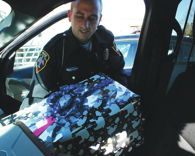 Urbana Police Officer Luke Hiltibran prepares to load a Christmas present for delivery. Officers with the Urbana Police Division will deliver presents Saturday as part of The Giving Christmas Tree program. Members of Fraternal Order of Police, Lodge 93, sought out children in need of an extra Christmas present this season. Lt. Josh Jacobs said presents will be delivered to 33 families and a little over 80 children.
