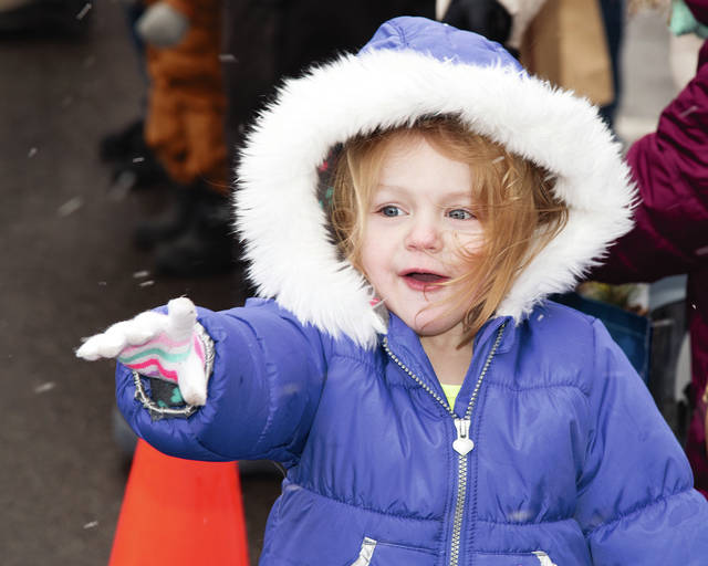 Isabella Nelson waves excitedly as the Christmas Parade carrying Santa Claus makes its way through Mechanicsburg on Saturday. See more pictures from the parade inside today's paper.