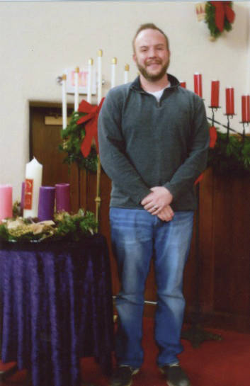 Rev, Beau Brown stands amid Christmas decorations in the sanctuary of First Presbyterian Church.