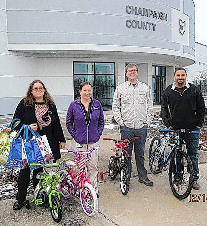 Champaign County Department of Job and Family Services staff display four bicycles donated by Bike Lady Inc. before CCDJFS Child Protective Services gave them to local foster children for Christmas. From left are Kristina Hawkey, Mandy Wilber, Zach Walden and Stephen Allen II.
