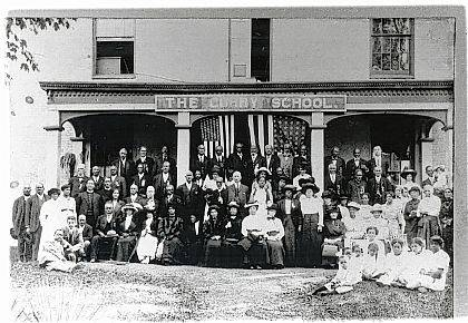 """This """"Then"""" photo of The Curry School was taken on the occasion (Sept. 20, 1913) of the reunion of black Civil War veterans and widows, sons and daughters from all parts of Ohio (Urbana Daily Citizen). Professor Elmer Curry is on the grass at the extreme left. This building at 325 E. Water St. was originally a residence owned by Philander B. Ross. It was purchased by the Urbana City Board of Education, which used it until 1898. Then Professor Curry acquired the property and moved the Curry Normal and Industrial Institute into the building. Over 2,000 mostly African-American students, youth and adults, were instructed in industrial skills, higher academics, and morality at the Institute. (Source: Sherry Virts, Champaign County Preservation Alliance)"""