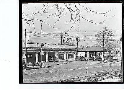 "In this ""Then"" photo, circa 1930, Barnhart Oil Company is shown in the 600 block of North Main Street, Urbana, looking west across the street. Note the signs indicating services provided by the filling station (CCHS #0004). This facility is on the west side of North Main Street, just south of the Pennsylvania and Erie railroad crossing of North Main Street. At the south end of this complex (not seen in photo) was the famous Crabill's Hamburger Shoppe."