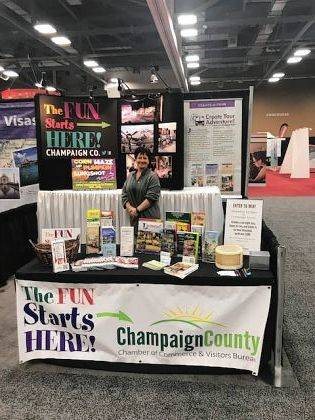 Chamber Coordinator and Visitors Bureau representative Susie Koennecke stands in the Champaign County Visitors Bureau booth at the AAA Travel Show in Columbus.