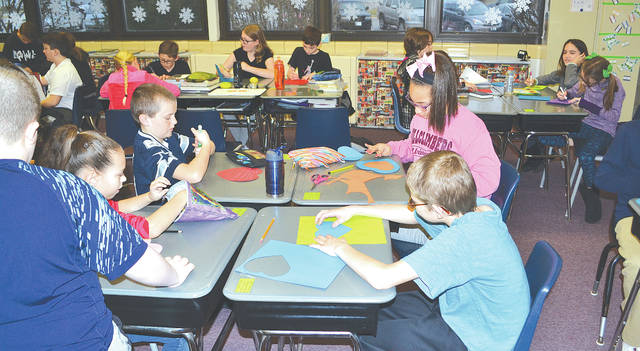 Students in Tyler Wisse's fifth grade class at Urbana East Elementary cut out hearts from construction paper on Wednesday. They plan to send valentines to soldiers stationed overseas.