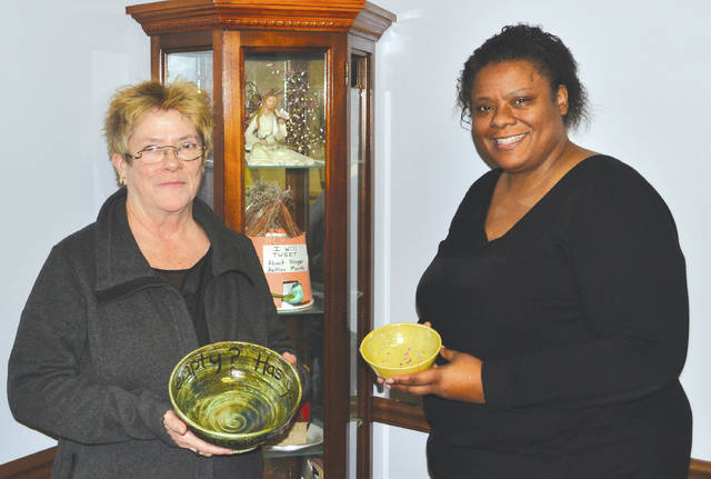 "Second Harvest Development Director Rosemary Bradley, left, and Executive Director Tyra Jackson hold two of the ""empty bowls"" that will be filled with soup at this year's Empty Bowls event on March 1."