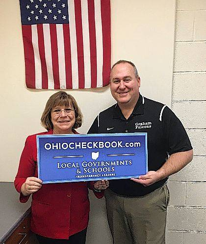 Graham Treasurer Judy Geers and Superintendent Kirk Koennecke are shown unveiling the district's new participation in a statewide initiative.