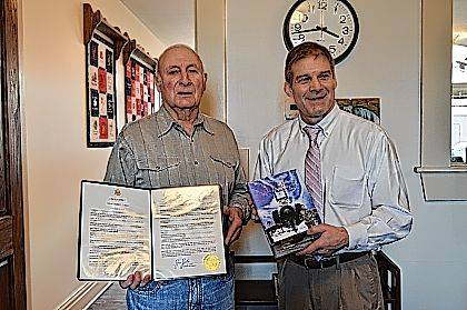 "Paul A. Kari, left, holds the proclamation he received from U.S. Rep. Jim Jordan (R-Urbana), who holds a copy of Kari's book, ""The Strength to Endure, a Memoir."""