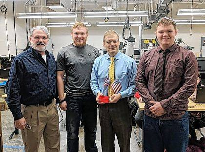 From left are Todd Bodey (instructor), Brian Ferguson (10th grade), U.S. Rep. Jim Jordan and Hunter Talbot (11th grade). Jordan received a flag holder and name plate the students designed and printed in class.