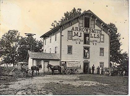 Circa 1880 photo of Arrowsmith Mills located on the east side of the Mad River just north of the southern Concord Township line in Champaign County, Ohio. A mill race diverted water from the river to the water wheel. Note the covered-like wagon with Arrowsmith Mills, Gold Lace Flour, W. H. Adlard, Urbana, Ohio written on the side. Building was erected 1844 and remodeled in 1877, as noted on the side of the building. Currently, this site is near the Birch Bark Canoe Livery on the Mad River. <em>The Champaign County Historical Society is an all-volunteer, not-for-profit organization that preserves, protects, archives and displays the artifacts that tell Champaign County's History. The Society operates on donations and dues and has a free public museum of history at East Lawn Avenue in Urbana.</em>