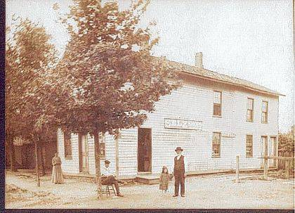 This circa 1900 photo (CCHS #A1852) is of a general store on Main Street in Cable. At one time the post office was in this building. The sign on the side of the building is an advertisement for Selz Shoes. Standing outside is a lady in a long dress. There are two gentlemen, one sitting on a chair under a tree and one standing holding a small girl's hand. Note the wooden hitching post at the side of the building. <em>The Champaign County Historical Society is an all-volunteer, not-for-profit organization that preserves, protects, archives and displays the artifacts that tell Champaign County's history. The society operates on donations and dues and has a free public museum of history at East Lawn Avenue in Urbana.</em>