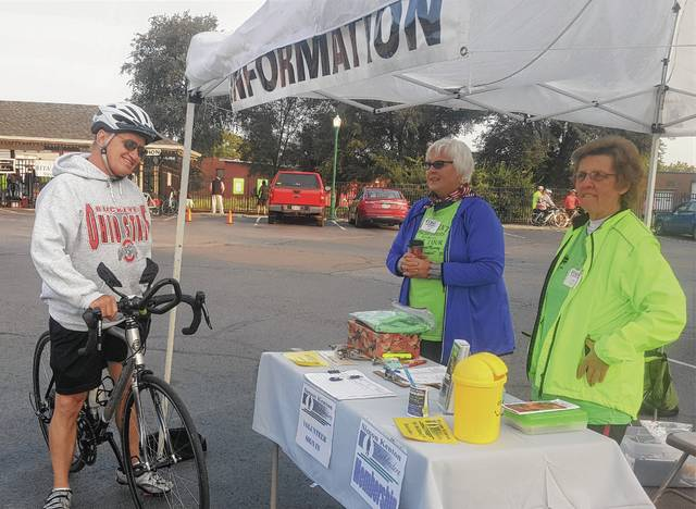 Pathfinder volunteers assist a bicyclist signing in for the Rita Larson Memorial Ride during the 2017 fund-raising event.