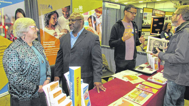 Associate Director of Extension at Central State University, Clarence Bunch, center, talks with EFNEP Cooperative Extension Coordinator at CSU Mary E. W. Kershaw, left, at the CSU Extension booth during the Ohio Ecological Food and Farm Association conference Feb. 16, while CSU Montgomery County Extension Agent Kevin McGhee, at right, talks with a conference attendee.