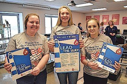 "Newton High School (Pleasant Hill) National Honor Society members Kacie Tackett, Paiton Miller and Halli Gipe wear the CBC ""Be The Red"" high school blood drive T-shirt designed by Newton graduate Aliya Stine."