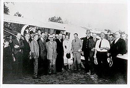 This is a photo (#0100) taken Oct. 24, 1934, of World War I Aviator Jimmy Mattern and an Urbana civic group. The group is next to the airplane Mattern flew into Urbana. He was touring under the sponsorship of the Pure Oil Co. At that time Urbana did not yet have an airport, so he landed in a pasture south of Urbana. County Prosecutor Grace Fern Heck represented county government. She was the first woman in the state to serve as prosecuting attorney. Also she was Ohio's first female municipal court judge. On her right is W.W. Rock, mayor of Urbana, and on her left is Mattern. Also in the photo is Warren Grimes (3rd from the left). Perhaps this event prompted him to consider establishing an airport in Urbana. <em>The Champaign County Historical Society is an all-volunteer, not-for-profit organization that preserves, protects, archives and displays the artifacts that tell Champaign County's History. The Society operates on donations and dues and has a free public museum of history at East Lawn Avenue in Urbana.</em>
