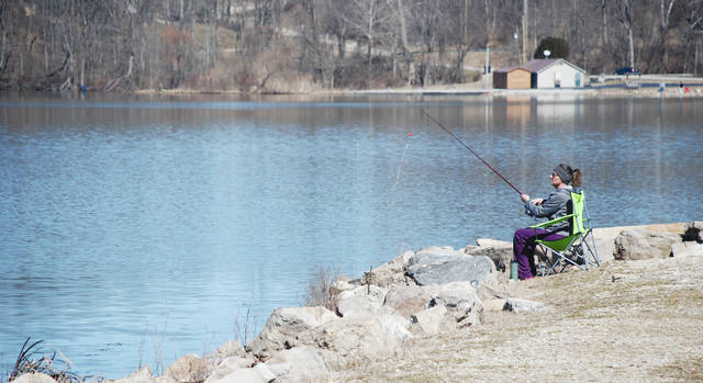 Wendy House of New Carlisle enjoys a sunny but brisk afternoon of fishing at Kiser Lake over the weekend. Pictured in the background is the Kiser Lake Marina.