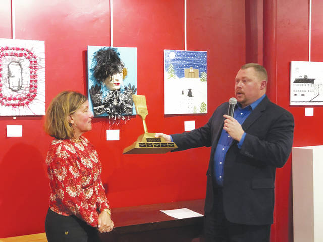 "Judge Brett Gilbert (right) presents the Golden Brush award trophy to winning artist Lin Giampetro during Friday night's ""Bad Art by Good People"" event."