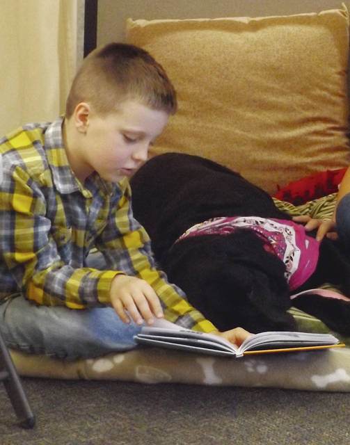 Graydon Edwards reads to Gypsy the dog during PAWS For Reading.