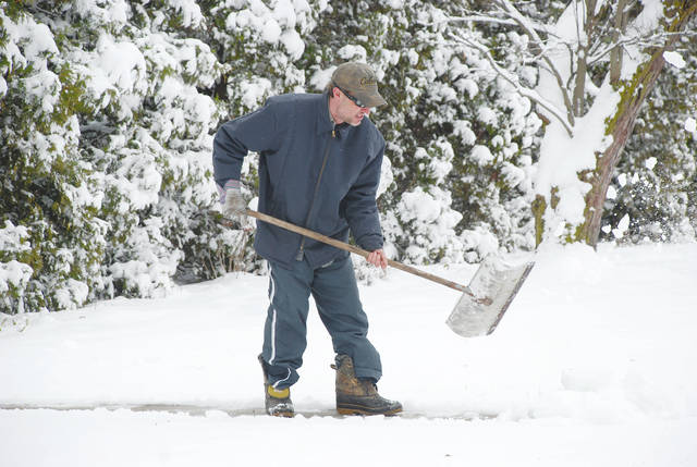 Brad Dearth of St. Paris clears snow from a South Springfield Street residence on Wednesday afternoon after several inches fell in Champaign County.
