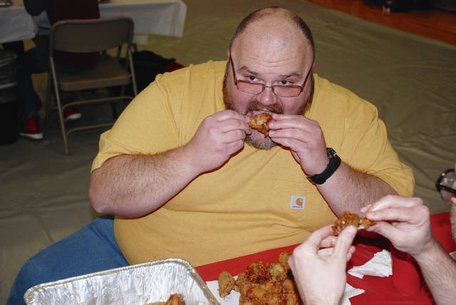 Graham Middle School teacher Mike Slone competes in a chicken wing eating contest to benefit the United Way. The contest was part of an assembly on Tuesday at Graham High School that included students and teachers.