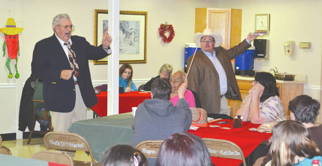 Auctioneer Ron Williams, left, and his son Kevin Williams, right, help raise $634.50 for the Alzheimer's Association by auctioning about 30 desserts at Urbana Health and Rehab's annual Chili Supper on Thursday.