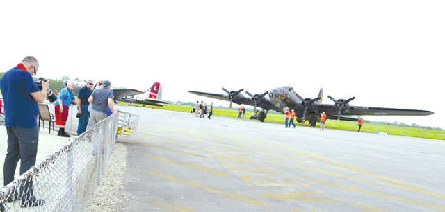 The top photo shows, from left to right, the Yankee Lady and the movie Memphis Belle B-17 bombers at Grimes Field on Monday. They will be staged there until they fly to Dayton on Wednesday morning for the unveiling of the restored Memphis Belle at the U.S. Air Force Museum on Thursday. The aircraft will return to Grimes Field after the unveiling and will be available for viewing Saturday and Sunday. The public is invited to Grimes Field today, Friday and Saturday to take photographs, enjoy music and refreshments, or to sign up for a short flight on either aircraft for $450. The second photo shows photographers and viewers at Grimes Field on Monday morning.