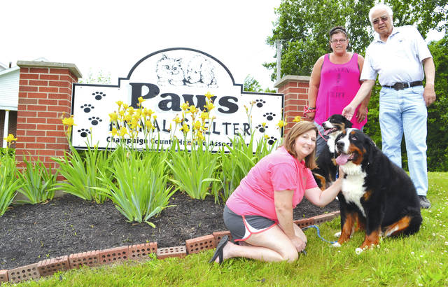 PAWS Animal Shelter Manager Toni Mossbarger, PAWS board President Dan Richardson and, kneeling, Personal Touch Landscaping and Consultations Inc. owner Tracy White, with her dogs Brutus and Monty, pose Tuesday outside PAWS, West U.S. Route 36, just west of Urbana. White said her company has provided mowing and snowplowing for PAWS for many years and that this year services will be donated to the non-profit organization. PAWS currently has one dog and 60 cats. Richardson said it costs about $7,000 a month to care for them all. Mossbarger said PAWS operates entirely on donations. In addition to money, donations of Purina Cat and Kitten Chow, canned pate-style cat food, bleach, dish soap, paper towels, hand soap, laundry soap and dryer sheets are welcome. For more info about donating or adopting, visit www.facebook.com/paws.urbana/