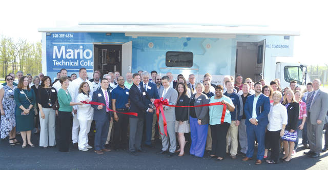 Eric Phillips, Marysville economic development director, cuts the ribbon at Marion Technical College's new mobile training lab Wednesday at the Honda Heritage Center in Marysville.
