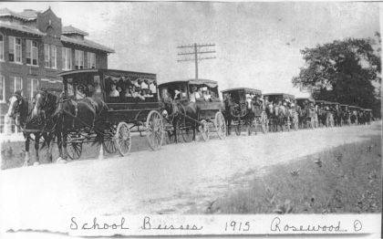 Then – This is a 1915 photo (CCHS #2001) of 10 horse-drawn school wagons in front of the Rosewood (Harrison-Adams Township) School in Adams Township. Based on other photos of horse-drawn school wagons, each wagon probably held 10-12 students. Horse-drawn school wagons were mostly superseded by gasoline-powered buses by about 1920. The Champaign County Historical Society thanks Deb Lewis of the Rosewood Grocery for sharing this photo.