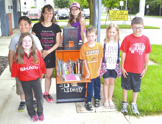 Diana Zimmerman, a volunteer art teacher for Triad Elementary School's after school program, worked with her group of nine first through fourth grade students to decorate several small lending libraries throughout eastern Champaign County. She and six of her students stood before the first such library outside the North Lewisburg Municipal Building on Tuesday, from left to right, Ziva Kitchen, 7; Jeremy Bary, 7; Zimmerman; Elliana Zimmerman, 10; Tristen Zimmerman, 7; Kile Penrod, 8; and Hayden Sheppeard, 8. Another lending library is located at the carryout in Mingo, one is at the pizza store in Cable, and a fourth is planned to be placed in Woodstock; anyone is encouraged to take a book or donate one at any location.