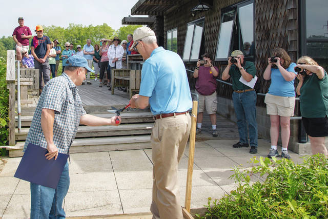Cedar Bog Association President Randy Rodgers (left) and Burt Logan cut the ribbon to dedicate the refurbished boardwalk at Cedar Bog on Saturday morning as supporters of the bog surround them. Logan is the executive director of the Ohio History Connection. Cedar Bog is a state historical site.