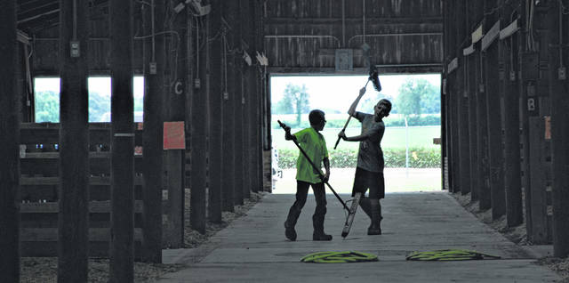 Arden McGuire of Urbana, left, and Weston Helman of Rosewood have a little fun while getting a head start on sweeping out the main aisle of the junior fair beef barn this week at the fairgrounds. The youths were preparing for the Champaign County Fair, which opens Friday, Aug. 3.