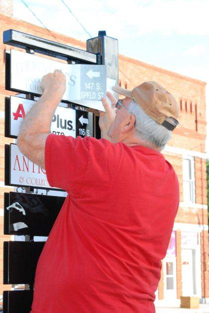 Richard Campbell, owner of Signs of the Times, installs vinyl signs onto steel posts in the village.