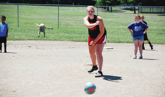 Morgan Hamby of Mechanicsburg pitches during YMCA kickball at the park with the kids this week. Cooler air and a lengthy prediction of rainy days ahead replaces the heat wave that lingered over Ohio during the early part of July.