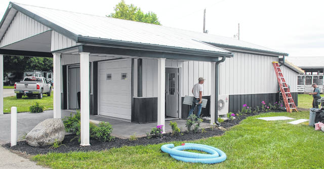 The Junior Fair Building named in memoriam for long-time fair board member Melvin Cook will feature new additions this year. A front porch has been built and additional space in the back has been added for the 2018 fair. In the photo, workers put the finishing touches on the additions this week at the Champaign County Fairgrounds. The fair opens today and continues through Friday, Aug. 10.