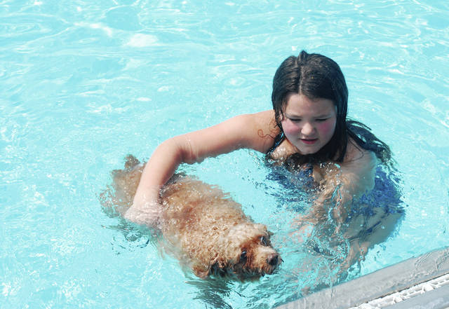 The Urbana City Pool at Melvin Miller Park closed for the season with a woof on Sunday. The annual Fido Swim, a fund-raiser to maintain Fido's Field Dog Park, was a success under sunny skies. In photo, eight-year-old Kenley Morrow helps her dog Izzy swim to the wall of the big pool. The Champaign County Citizens for Canines (CCCC), a 501(c)(3) nonprofit, is responsible for all of the amenities at the dog park. CCCC finances the repairs and maintenance of Fido's Field.