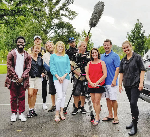 "Local Realtor Paige Duff (at left of camera) poses with the production crew from Left Right LLC of New York City and two of the the local homebuyers to be featured on the show. They just wrapped up shooting two new episodes to air later this year on HGTV's ""Island Life"" reality show."