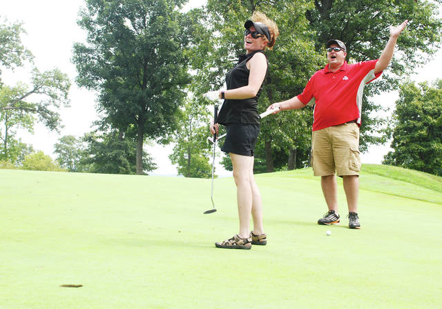 The Annual Bill Butler Champaign Open golf tournament was held at the Urbana Country Club on Wednesday. Proceeds from the long-running event are held in a separate account for any consumer served by CRSI who has unexpected expenses. In the photo, Leann and Dustin Wallen celebrate sinking a putt during the tournament.