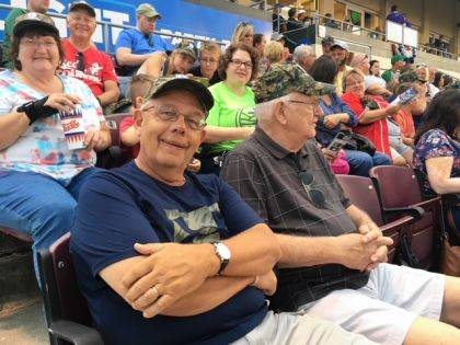 A capped and smiling Ed Hardin, front center, recruited 41 baseball fans from the Urbana Church of the Epiphany and the Mechanicsburg Church of Our Saviour for an evening of fun at a Dayton Dragons game at Fifth Third Field. Next to Hardin is Ron McFarland and in the row above are, from left, Cathy Murray, Isaac Waddell and Angela Murray. Seated in the top row are Todd, Sophie and Will Boeck.