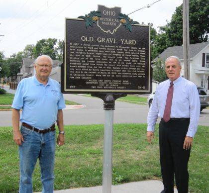 "Dan Walter, left, president of the Champaign County Historical Society, and Kerry Brugger, city Director of Administration, stand by the re-installed Ohio Historical Marker at Urbana's first graveyard. In 2014 the historical society, the city and others dedicated the marker at the northeast corner of Kenton and Ward streets to commemorate the graveyard (1805-1855) and the War Council of 1812, which took place about 100 yards to the west. Last year the marker suffered significant damage and was returned to the manufacturer for repair. ""We sincerely appreciate Director Brugger and the city of Urbana taking the initiative to repair and re-install this important marker,"" said Walter. ""People need to understand that considerable research and monies go into the creation of Ohio Historical Markers and that they need to be protected."""