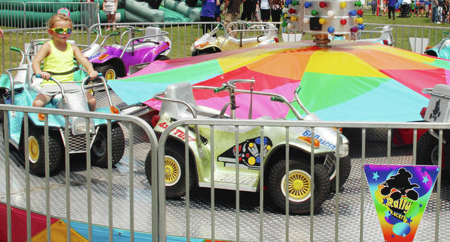 Elizabeth Goodlin, age 4, rides solo on the Rally Racers attraction at the Champaign County Fair over the weekend.