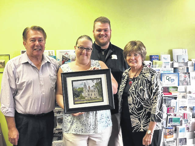 From left are Elton Cultice, Visitors Bureau committee member; Mandy Davis holding her winning photo; Adam Moore, Visitors Bureau committee member; and Sandy Gonzalez, Visitors Bureau committee member.