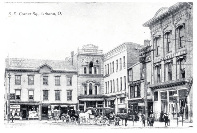 "Then – This is a circa 1905 photo (#0135) of the southeast corner of Monument Square, Urbana. A drug store is at the Scioto Street corner with ""Alabastine"" in the window. Painted on the roof of this building was ""DRUGS-PAINTS-OILS."" Note the public drinking fountain in front of the drug store. A dentist's office is above the drug store. Next door is a bakery. In the corner is a harness shop. Later Harmstead & Holding store was located here. On the south side is a photographer's studio. Note the slanted skylight window providing the best light for taking photos. This building burned about 1960 and was replaced by a one-story building that became the location of the AAA office. At the South Main Street corner is the Hitt & Fuller Dry Goods Store."