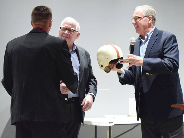 Urbana High School Athletic Director Daniel Shay (left) receives Tom Watson's 1950 Ohio State football helmet from Watson's sons, Andy (middle) and Alan, during Thursday night's George Scott Ring of Honor ceremony held at BrownRidge Hall. Tom Watson, a former UHS star athlete and coach, was inducted posthumously. The Watsons donated the helmet to Urbana High School.