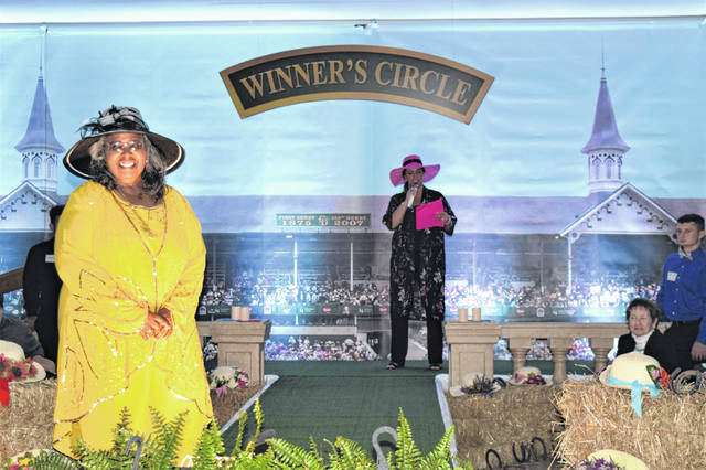 "Ce Greene models in ""Kentucky Derby Style"" during Fashions to a Tea on Oct. 11 at the Champaign County Fairgrounds. Pictured in background is mistress of ceremonies Elle Spinner."