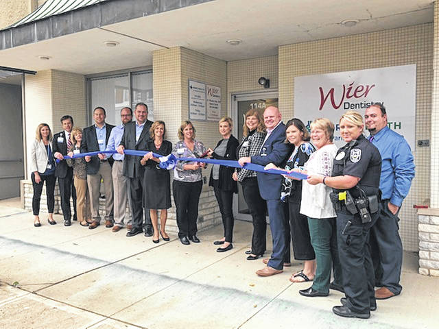 The Champaign County Chamber hosted a ribbon-cutting Oct. 2 to welcome the official opening of Mercy Health Clinic in St. Paris. From left are Tracey Short, Alex Rintoul, Marianne Potina, Alex Groshans, Ben Merrick, Matt Caldwell, Jamie Houseman, Nichole Clark, Jamie Kennedy, Shannon McCowan, Lee Syphus, Emily Purk, Brenda Cook, Brandon Nichols and Chief Erica Barga.